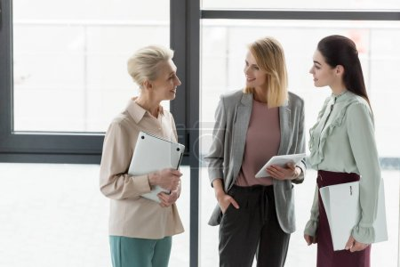 Photo for Smiling beautiful businesswomen talking in office - Royalty Free Image