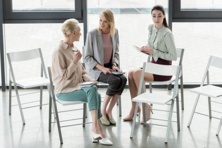 professional businesswomen sitting on chairs and talking in office