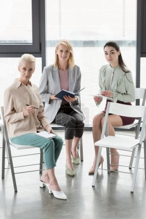 beautiful businesswomen sitting on chairs and looking at camera in office