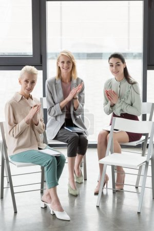 beautiful stylish businesswomen applauding in office