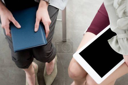 cropped image of businesswomen holding notebook and tablet in office