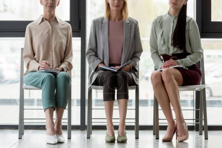 cropped image of businesswomen sitting on chairs during meeting in office