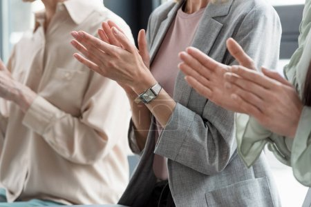 cropped image of businesswomen applauding in office