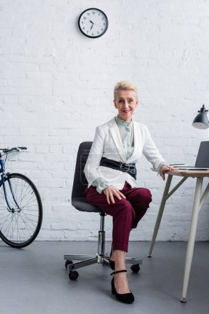 élégante femme d'affaires senior avec ordinateur portable au bureau moderne