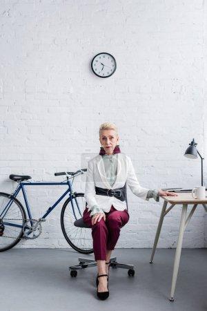 Photo pour Élégante femme d'affaires senior travaillant dans des bureaux modernes avec vélo - image libre de droit