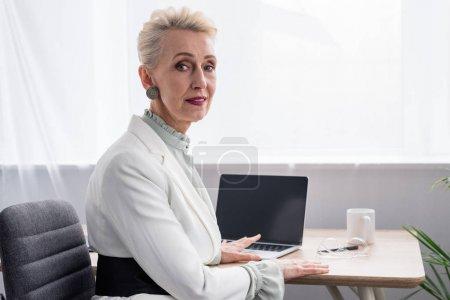 Photo pour Séduisante femme d'affaires senior travaillant avec ordinateur portable au bureau moderne - image libre de droit