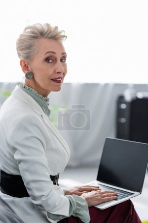 attractive senior business woman using laptop with blank screen