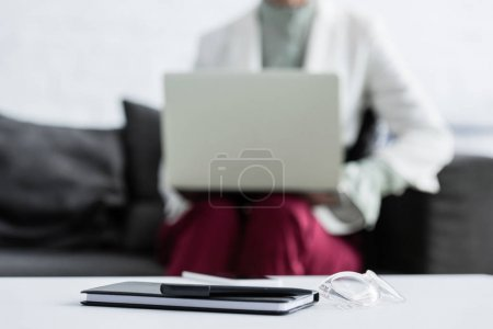 selective focus of businesswoman using laptop, diary, pen and glasses lying on table on foreground