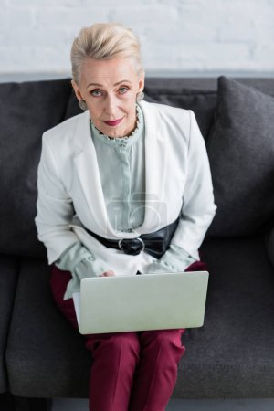 overhead view of beautiful senior business woman using laptop on sofa