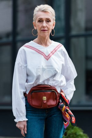 fashionable senior woman in trendy outfit posing with belt bag