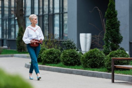 senior woman in trendy outfit with waist bag walking in park