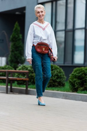 smiling senior woman in trendy outfit with waist bag walking in park