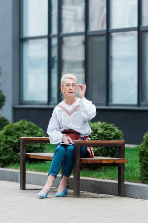 fashionable senior woman with diary sitting on bench