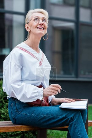 dreamy senior woman in trendy outfit writing in diary while sitting on bench