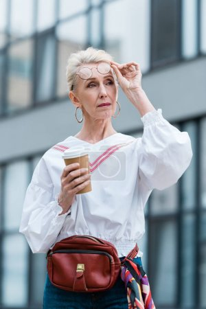 stylish senior woman in trendy glasses holding disposable cup of coffee
