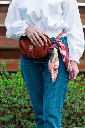 cropped view of fashionable woman in trendy outfit with waist bag and scarf