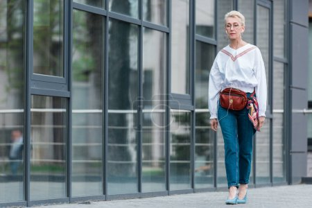 beautiful senior woman in stylish outfit listening music with earphones while walking in city