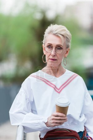senior woman in trendy outfit with coffee to go walking in park