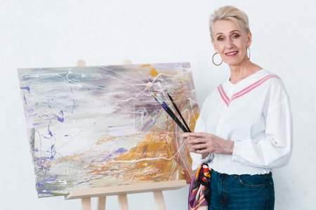 senior elegant female artist holding paintbrushes and standing near painting on easel in workshop