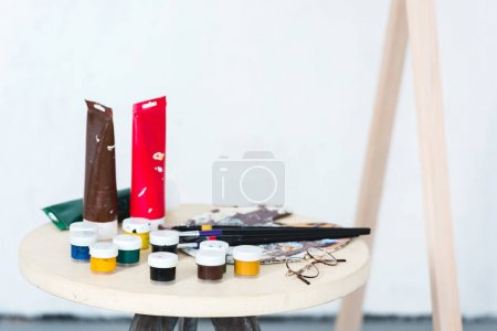 paintbrushes, palette and paints on stool in artistic workshop