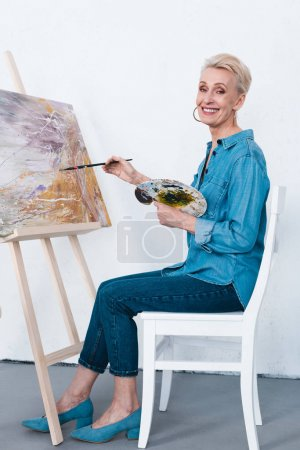 senior woman painting on easel with paintbrush and palette in workshop