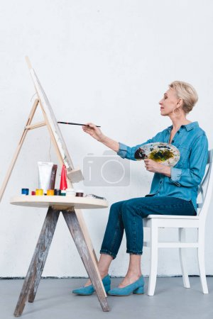 senior woman painting on easel in artistic workshop