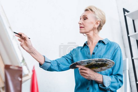 beautiful senior woman painting with palette in artistic workshop