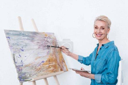 Photo pour Senior gai femme peinture avec palette sur chevalet en atelier - image libre de droit