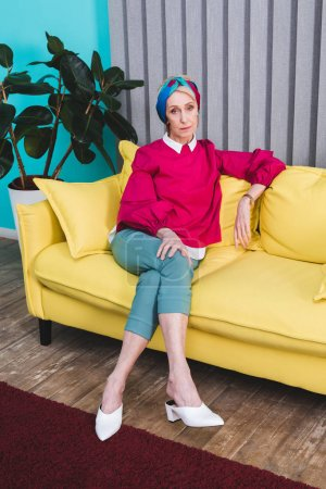 Photo for Beautiful senior woman sitting on yellow sofa - Royalty Free Image