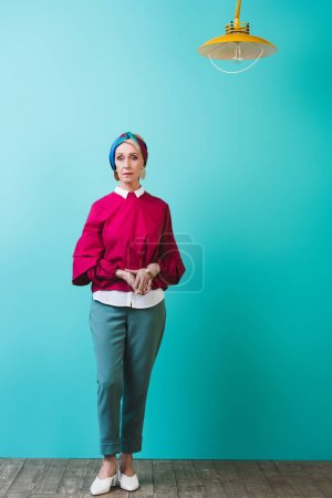 beautiful senior woman standing in room with turquoise wall and lamp