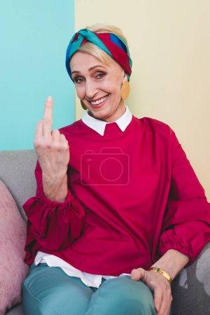 smiling senior woman showing middle finger