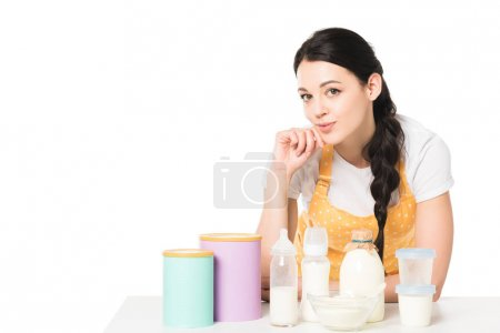 smiling young woman in apron at table with children food and milk isolated on white background