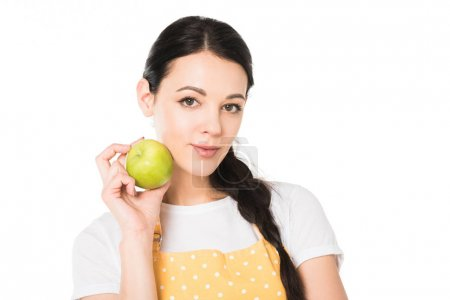 young woman in apron holding apple near cheek isolated on white background