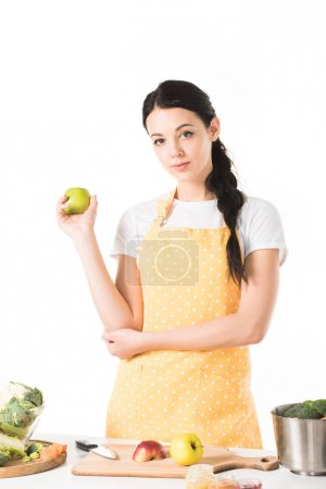 woman holding apple near table with cutting board, saucepan, apples and vegetables
