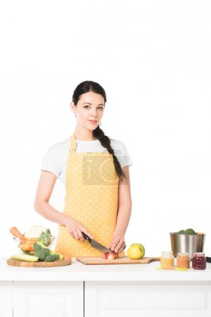 young woman cutting apple by knife at table isolated on white background
