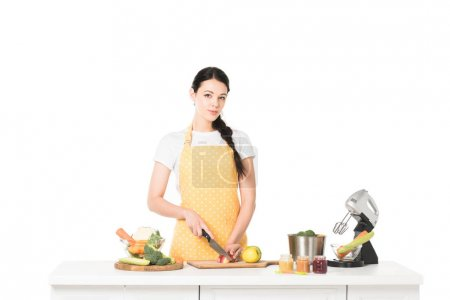 young woman in apron cutting apple at table with mixer, vegetables, jars with puree and saucepan