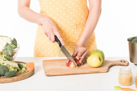 cropped image of woman in apron cutting apple by knife isolated on white background