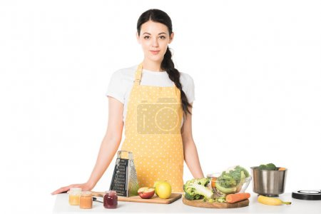 Photo for Woman in apron standing at table with fruits, vegetables, cutting boards, grater, jars with puree and saucepan - Royalty Free Image