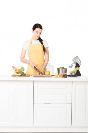 woman in apron cutting apple at tabletop with mixer, saucepan, jars, fruits and vegetables