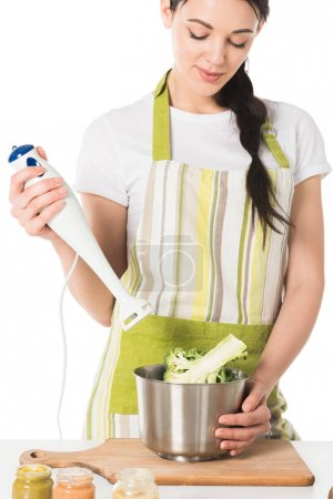 Photo for Young woman with hand blender in hand at table with broccoli in saucepan - Royalty Free Image