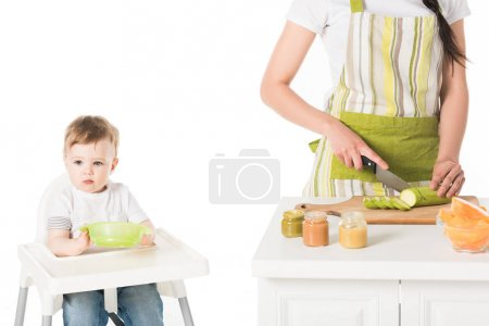 cropped shot of mother in apron cutting zucchini and son sitting in highchair with plate