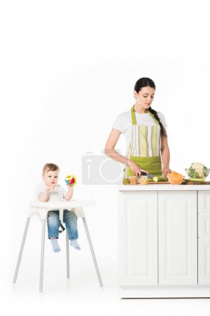 baby boy in highchair with toy and mother cutting zucchini at table isolated on white background