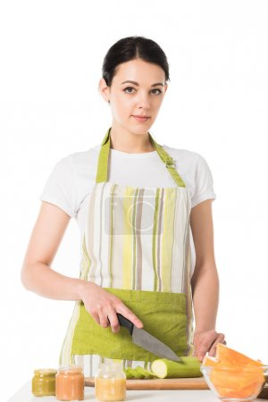 young woman in apron cutting zucchini by knife isolated on white background