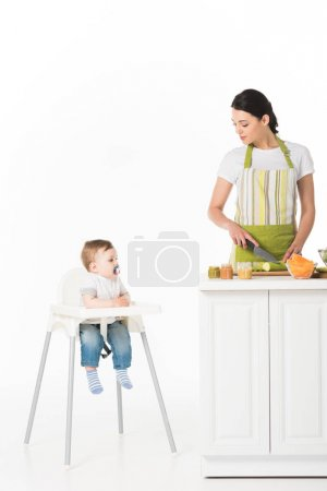 woman in apron cutting zucchini and looking at little son with baby pacifier sitting in highchair