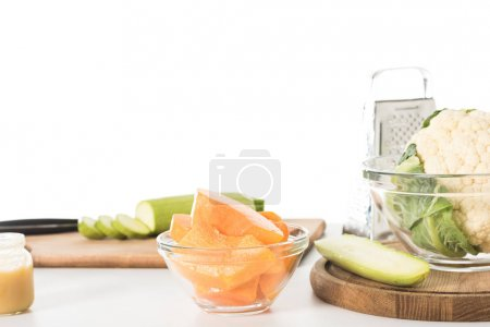 closeup shot of bowl with pumpkin slices, zucchinis, cutting boards, grater and bowl with cauliflower isolated on table