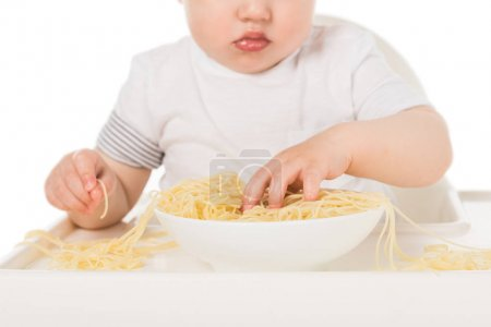 cropped shot of baby boy eating spaghetti by hands and sitting in highchair