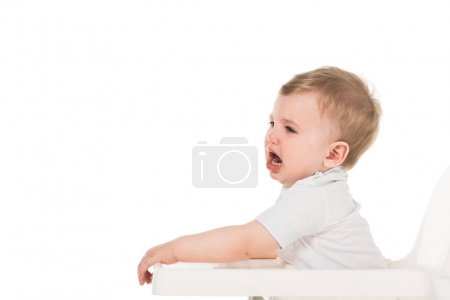 side view of crying baby boy in highchair isolated on white background