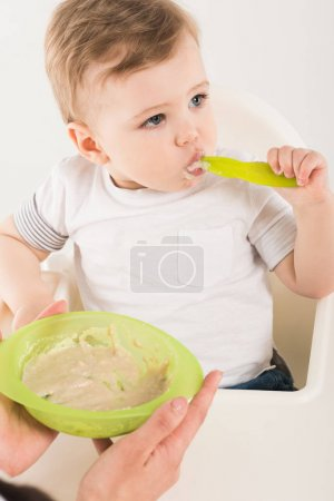 cropped shot of mother holding plate with food and baby boy with spoon in highchair