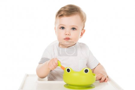 adorable little boy eating from plate in form of frog and sitting in highchair