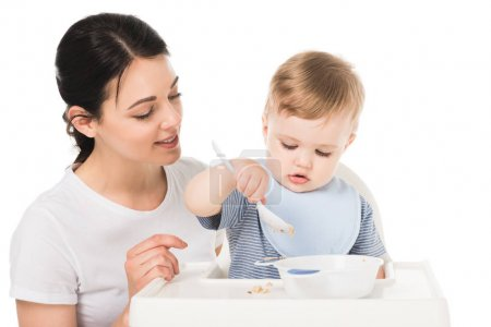young woman with son in bib eating and sitting highchair isolated on white background